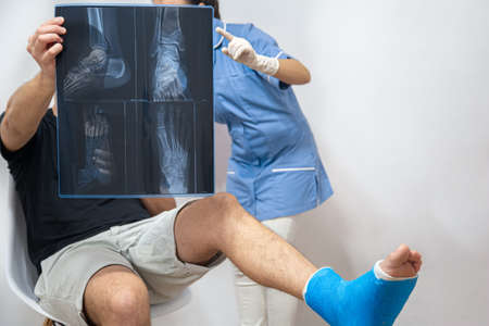 Female doctor in a blue medical gown explains to a male patient with a broken leg the result of an x-ray.