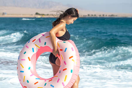 A cheerful woman with a donut-shaped swimming circle by the sea. The concept of leisure and entertainment 版權商用圖片