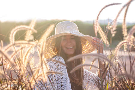 Portrait of a young woman in the sun, sitting in a field, dressed in summer clothes and a hat. Stockfoto