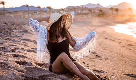 Beautiful boho model in a swimsuit with a white Cape with a hat on her head poses on the beach at sunset 版權商用圖片