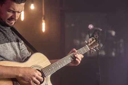 Guitarist playing acoustic guitar against blurred dark background at concert close up. 版權商用圖片