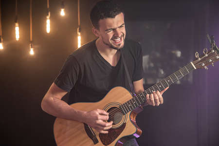 Happy guitarist in a black t-shirt plays an acoustic guitar at a concert against a blurred black background. Close up.