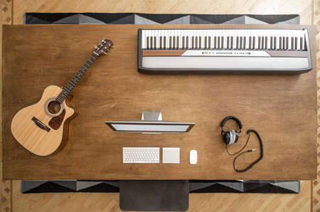 On a large wooden table there is a stationary computer, musical keys and studio headphones for sound recording. Top view.