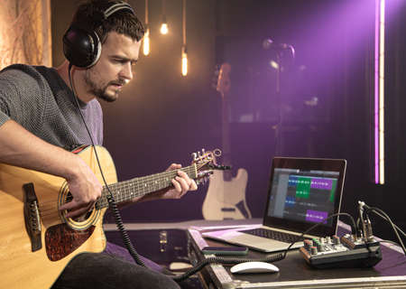 A male guitarist plays the guitar with headphones connected to a sound mixer. Digital waveform on laptop monitor, sound recording concept. 版權商用圖片