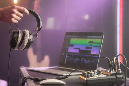 Professional headphones connected to music mixer and laptop on blurred background of music studio with studio light close up.