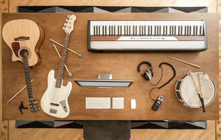 Acoustic guitar, bass guitar, snare drum, drum sticks, headphones, computer and musical keys on the background of a wooden table in a music studio top view.