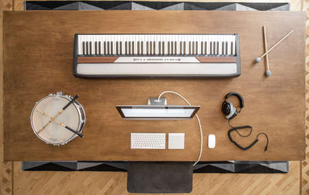 Musical keys, sticks, drum, headphones and a computer on a wooden table. Workplace of a musician to work on sound.