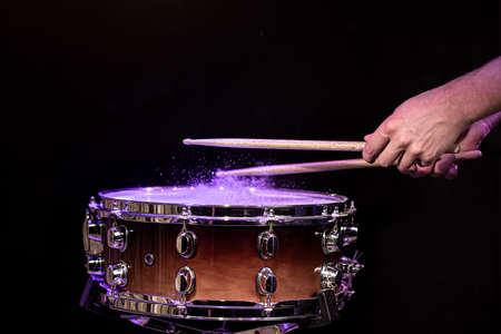 Drummer playing drum sticks on a snare drum on black background close up. 版權商用圖片