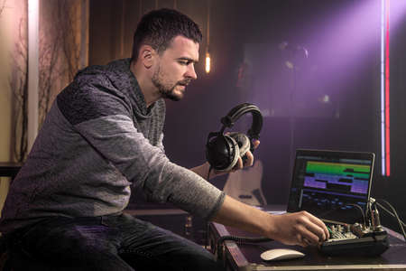 A sound engineer with studio headphones in hand sets up a sound mixer in a music studio with studio lights. The concept of professional recording.