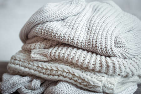 Close up of neatly folded knitted items of pastel color on a light background. Фото со стока