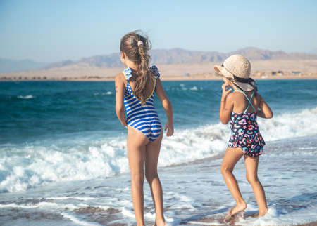 Two little girls play along the beach by the sea. The concept of friendship and recreation.