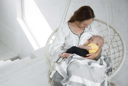 Happy mom feeds a baby in a white hammock with a blanket on the background of a white room. Cope space.