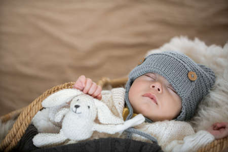 Portrait of a sleeping baby in a warm knitted hat with a knitted toy in the handle on a blurred background close up, copy space.