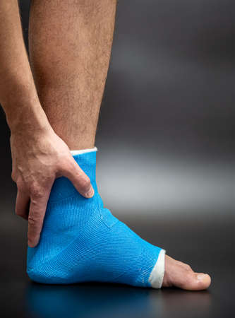 Blue splint ankle. Bandaged leg cast on male patient on dark blurred background. Sports injury concept.