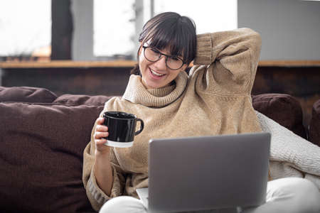 A young beautiful girl sits on the sofa at home with a cup of drink and cheerfully looks at the computer screen. The concept of video communication and communication at a distance.