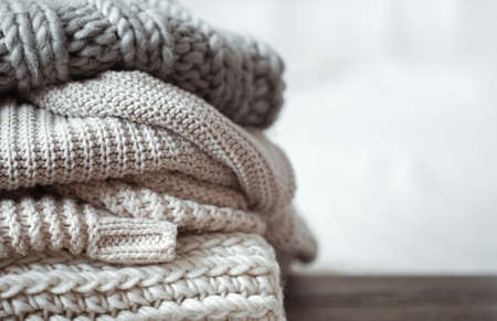 Close up of neatly folded knitted items of pastel color on a light background.