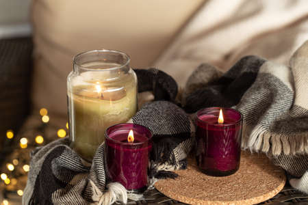 Close up of burning candles in candlesticks with details of home comfort. Stock Photo