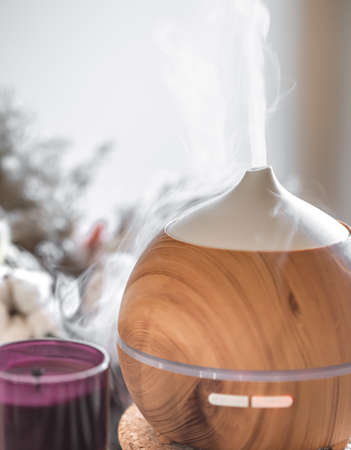 Aroma oil diffuser lamp on a table. Aromatherapy and health care concept.