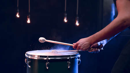 The percussionist plays with sticks on the floor tom in a dark room with beautiful lighting. Concert and performance concept.
