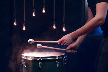 The percussionist plays with sticks on the floor tom in a dark room with beautiful lighting. Concert and performance concept. Stockfoto