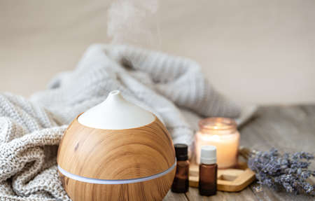 Modern aroma oil diffuser on wood surface with knitted element, candle and lavender oil on a blurred background.