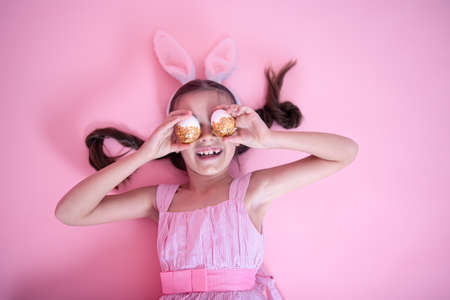 Little girl with Easter bunny ears posing with festive Easter eggs lying on a pink studio background.