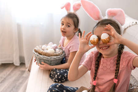 Little sisters with bunny ears, with Easter eggs at home on the couch. The concept of preparing for the Easter holiday.