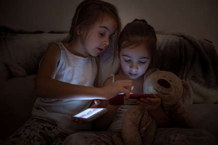 Little girls watching smartphone in bed, kids using phone and play game, using mobile, addicted game and cartoon.