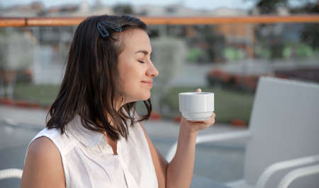 An attractive young woman is enjoying her morning coffee on an outdoor summer terrace. Rest and relaxation concept.