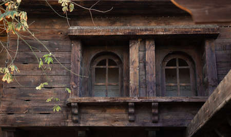 Old abandoned wooden house with wooden windows and shutters.