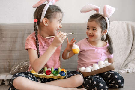 Little sisters in bunny ears paint Easter eggs on the sofa at home. The concept of preparing for the Easter holiday.