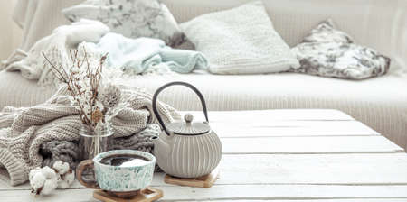 A teapot and a beautiful ceramic cup with decor details in a hygge style living room. The concept of home comfort and modern style.