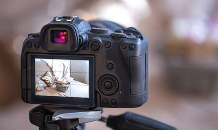 Close up professional digital camera on a tripod on a blurred background. The concept of technology for working with photos and videos. Stockfoto