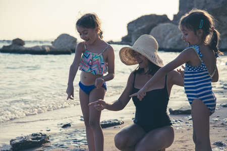 Mom and two little daughters are walking along the seashore in swimsuits, looking at something interesting in the sand. Family vacation at the sea.
