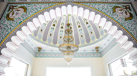 Large golden chandelier on a variegated ceiling with islamic traditional religious ornament.