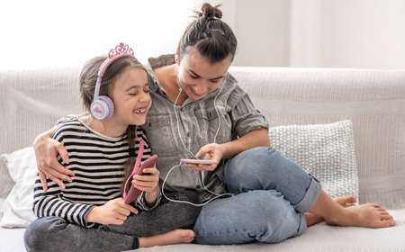 Cheerful mother and daughter are resting at home, listening to music on headphones. The concept of a happy family and friendly relations. Stock Photo
