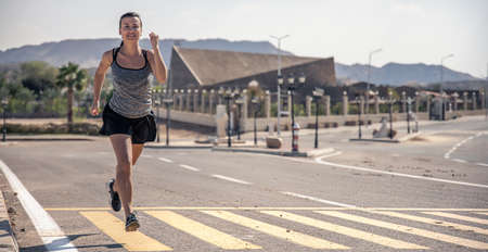 A young woman in a T-shirt and shorts runs along an asphalt road on a hot morning.