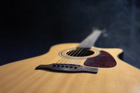 Classic acoustic guitar body in dark copy space. 免版税图像