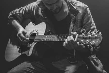 The musician plays the guitar while sitting in a dark room.