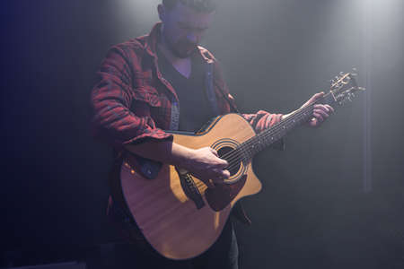 A man plays an acoustic guitar at a partially lit concert.