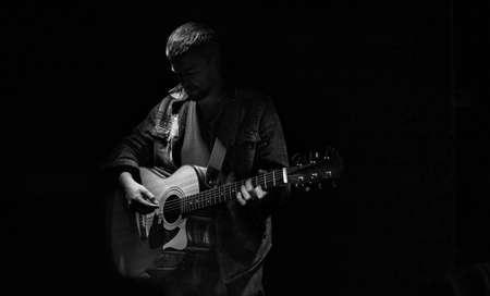 Male guitarist playing acoustic guitar in dark room. Zdjęcie Seryjne