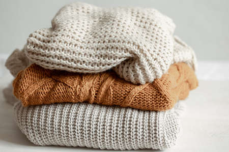 A stack of neatly folded warm knitwear, wool close up.