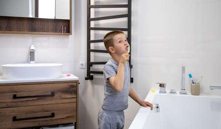 Cute little boy brushing teeth in a cozy bathroom interior.