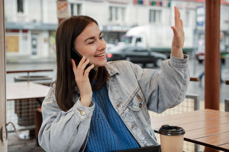 Street portrait of a cheerful young woman on the terrace of a cafe, who is waiting for someone.