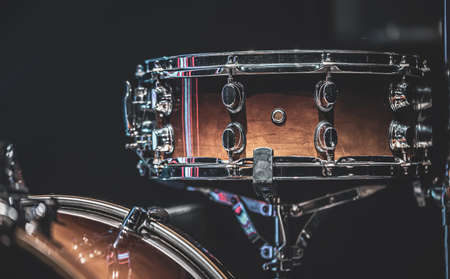 Close-up of a snare drum, percussion instrument on a dark background.