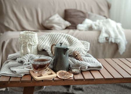 Cozy home still life with a cup of tea and details of autumn home decor in the interior of the room. Banque d'images