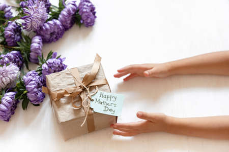 Baby hands and gift box to mom for mother's day, on a white background with fresh chrysanthemum flowers.