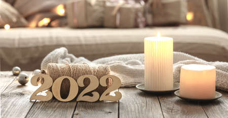 Home Christmas composition with decorative wood 2022 numbers, candles, and decor details on a blurred room interior background.