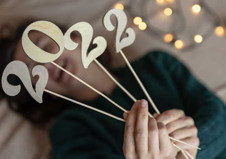 Close-up of wooden numbers 2022 on sticks in the hands of a girl, on a blurred background. Banque d'images