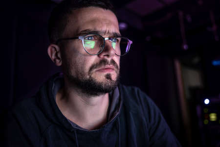 A man stares intently at a computer screen in the dark at night, copy space.